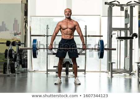 Muscular man lifting dumbbell and looking in camera Stock photo © dash