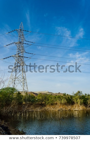 Stockfoto: Electrical Transmission Tower Electricity Pylon Beside A Lake