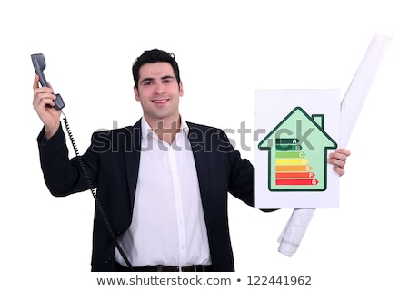 Stock photo: commercial agent holding an energy consumption label and a phone