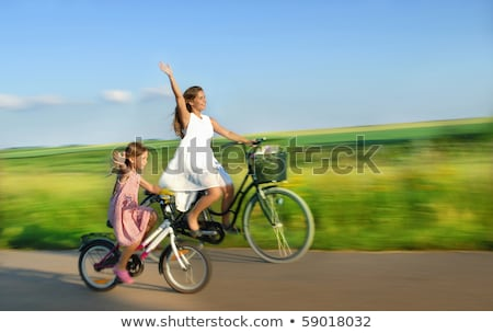 Stock photo: country girl with bicycle and flowers