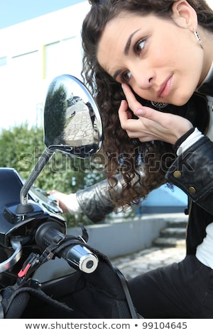 woman applying eye make up with the help of her motorcycles mirror stock photo © photography33