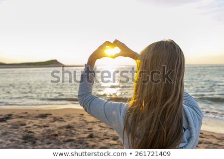 girl holding hands in heart shape at beach stock photo © elenaphoto