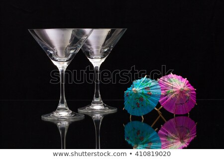 Two empty glasses of champagne with paper umbrellas Stock photo © CaptureLight