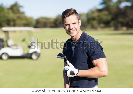 Male golfer standing with a golf club and smiling Stock photo © imagedb