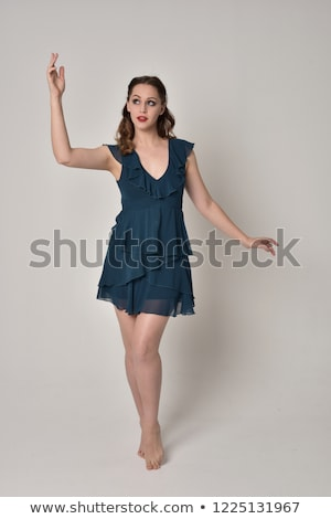 young brunette lady in blue dress posing on grey background stock photo © victoria_andreas