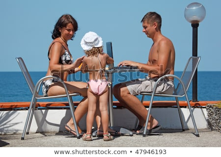 Family of three people resting on sea. On warm sunny day they sit outdoors at a table with laptop. Stock photo © Paha_L