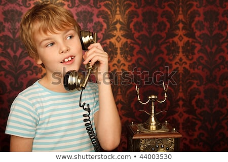 portrait of boy in t shirt talking to an old phone against wall stock photo © paha_l