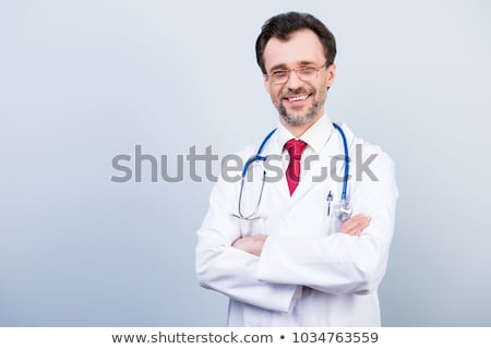 Happy male doctor standing with arms folded  Stock photo © deandrobot