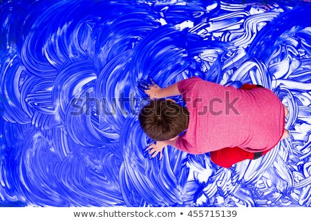 Top down view on boy smearing hands in paint Stock photo © ozgur