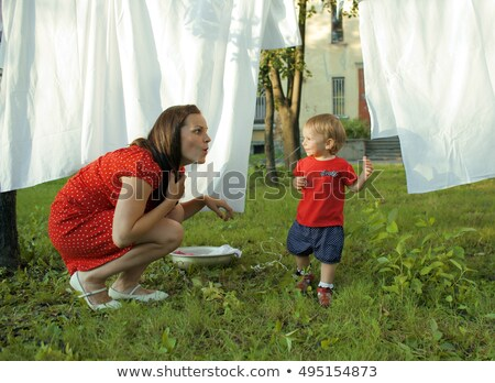 woman with children in garden hanging laundry outside playing with cute baby girl toddler lifestyl stock photo © iordani