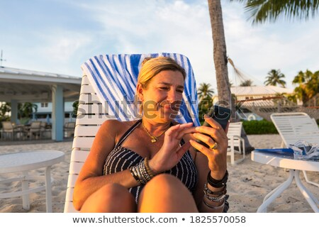 Woman in swimwear lounging on beach in her vacation Stock photo © Kzenon