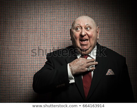 Senior man adjusting tie against dogtooth check background Stock photo © IS2