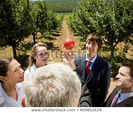 Man showing apple to group in orchard. Stock photo © IS2