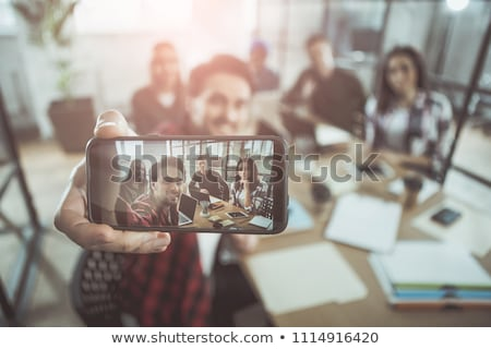 a young girl is sitting at the desk in the office and taking photos on the phone stock photo © traimak