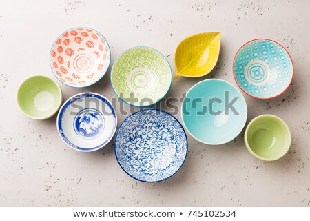 Collection of empty colorful decorative ceramic bowls on grey stone background. Stock photo © dash