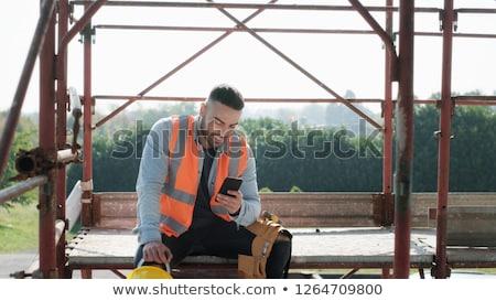 Człowiek pracy budowa uśmiechnięty smartphone osoby Zdjęcia stock © diego_cervo
