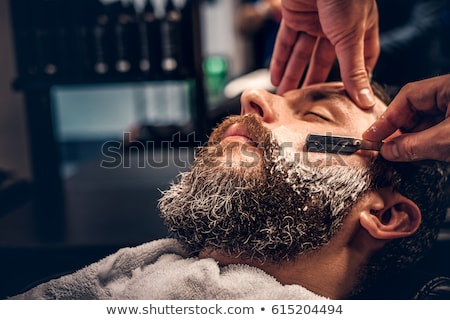 Young barber shaving with straight razor Stock photo © Kzenon