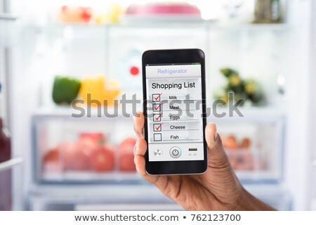 woman using mobile phone in front of refrigerator stock photo © andreypopov