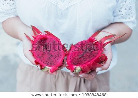 dragon fruit in beautiful female hands on a green background stock photo © galitskaya
