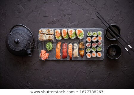 assortment of different kinds of sushi rolls placed on black stone board stock photo © dash