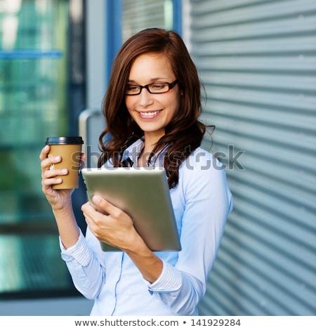 Mulher jovem potável café ebook leitor sofá Foto stock © boggy