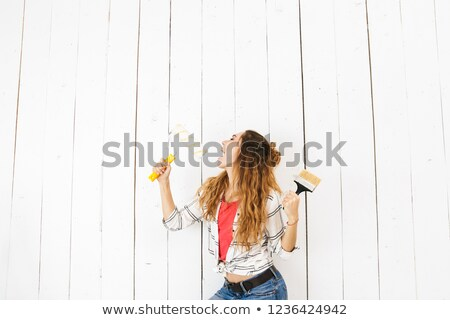 Image of joyous woman 20s holding roller and brush, while painti Stock photo © deandrobot