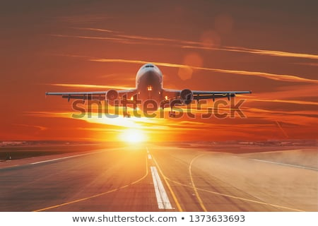 passenger airplane is flying over clouds at sunset stock photo © denbelitsky