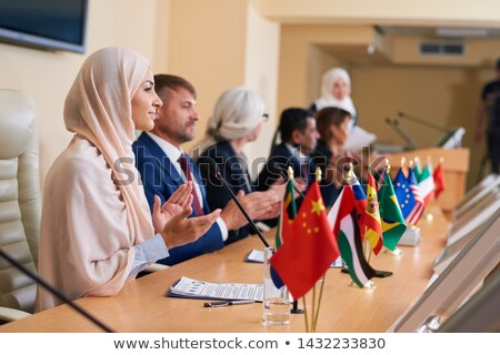 Young female delegate in hijab and her foreign colleagues applauding Stock photo © pressmaster