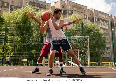 One of basketball players with ball trying not to let his rival take it away Stock photo © pressmaster