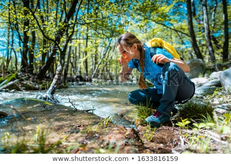Stock photo: Woman refreshing herself with fresh water from creek while hiking