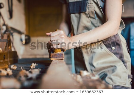 Close-up on hand of woman carpenter with wood planer Stock photo © Kzenon