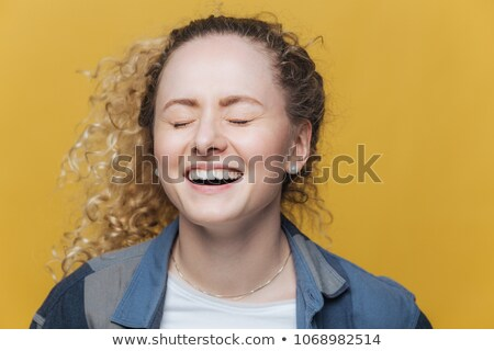 Overjoyed beautiful female laughs joyfully as hears good joke, smiles broadly, keeps eyes shut, has  Stock photo © vkstudio
