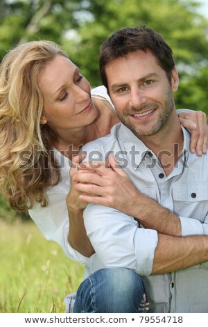 Stock photo: Happy couple sat outdoors touching hands