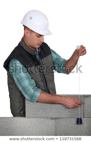 Mason using plumb line, studio shot Stock photo © photography33