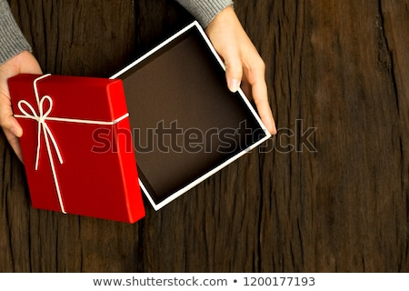 hand holding ribbon and open gift box stock photo © ozaiachin