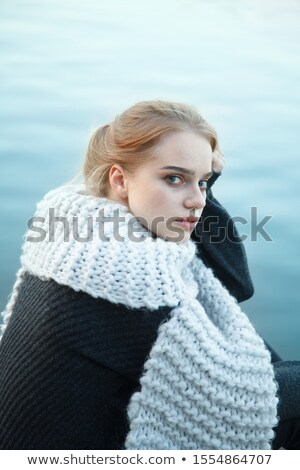 Woman coated in scarf sitting on beach Stock photo © vetdoctor