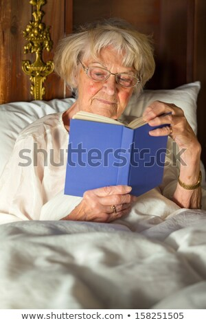Elderly woman in her nightgown reading in bed Stock photo © belahoche