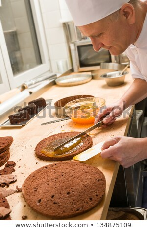 Cook making layer chocolate cake with marmalade Stock photo © CandyboxPhoto