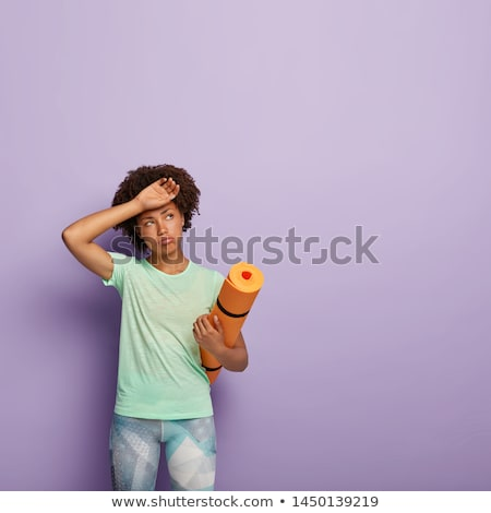 Young woman carrying exercise mat looking sad stock photo © bmonteny
