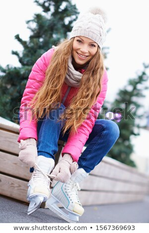 Happy young woman tying her ice skates in winter Stock photo © bigjohn36