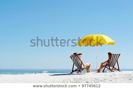 Kadın güneşlenme güverte sandalye plaj yandan görünüş Stok fotoğraf © AndreyPopov