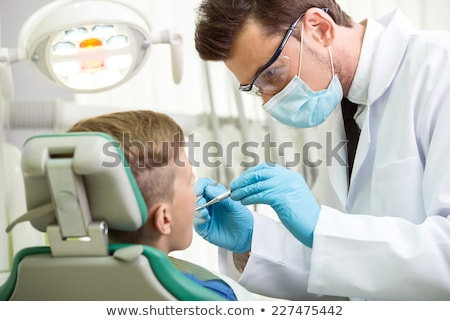 Stock photo: Pediatric dentist examining a little boys teeth in the dentists