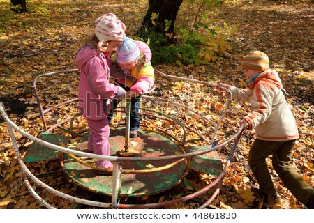 two girls and one boy play on roundabout in autumnal park stock photo © paha_l