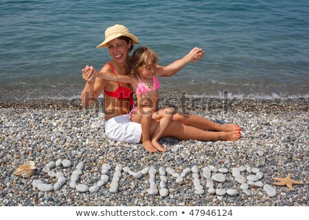 Mother and daughter sitting on beach near water. Before them of stones piled