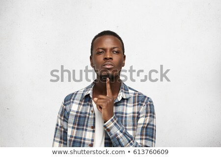 Pensive doubtful young man holding hand on his chin  Stock photo © deandrobot