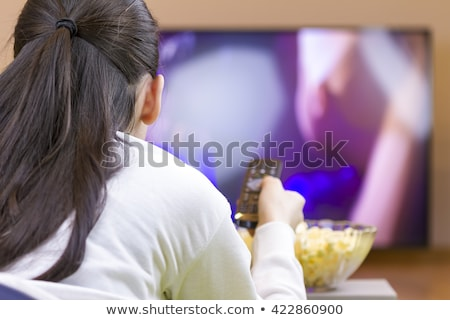 happy tennager girl laying down and watching tv Stock photo © manaemedia