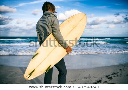 man with his surfboard standing and looking at the horizon stock photo © deandrobot