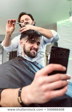 молодым человеком парикмахер телефон сидят Сток-фото © deandrobot