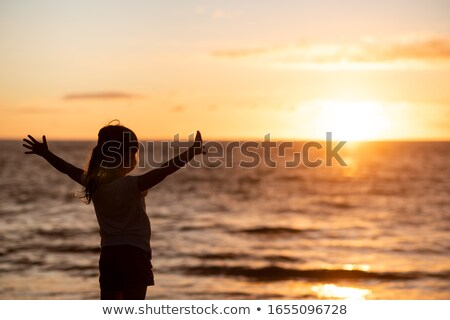 Girl posing in the water at sunset, real water stock photo © konradbak
