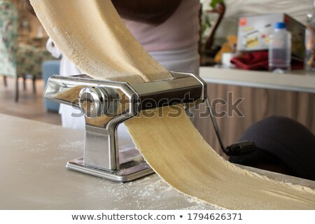 fresh egg tagliatelle being rolled in a pasta machine stock photo © monkey_business